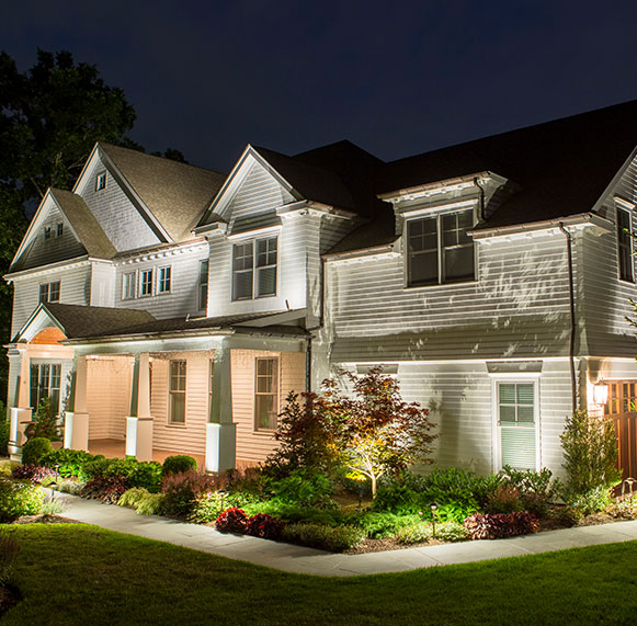 Home exterior lit with landscape lighting